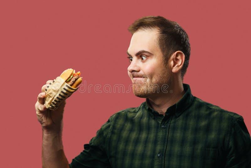Un giovane tiene in mano un hamburger e lo guarda con appetito immagine stock libera da diritti