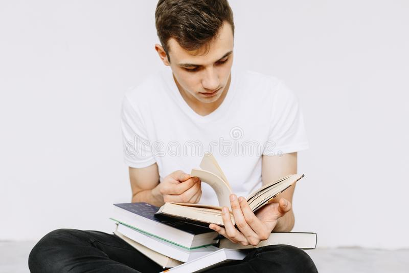 Un giovane tipo è libri di lettura Uno studente, uno scolaro che prepara studiare Fondo bianco isolato immagine stock libera da diritti