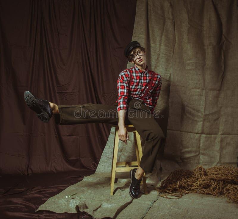Un giovane tipo attraente si siede su una sedia con una gamba sollevata livello immagine stock libera da diritti