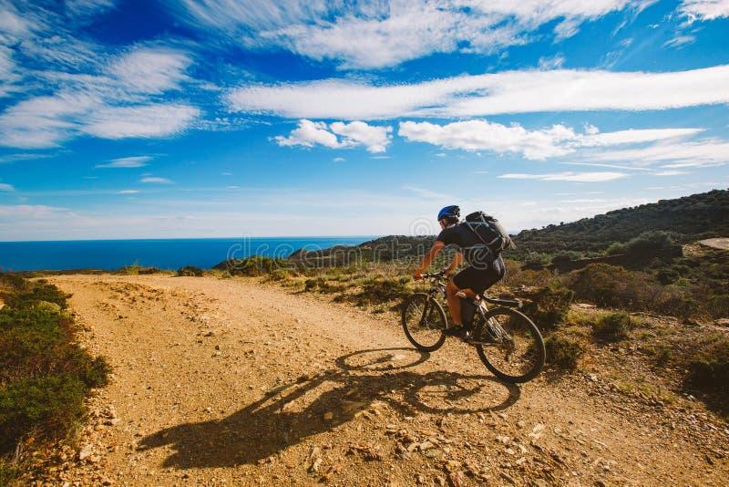 Un giovane tipo che guida un mountain bike su un itinerario della bicicletta in Spagna sulla strada contro lo sfondo del mar Medi fotografie stock