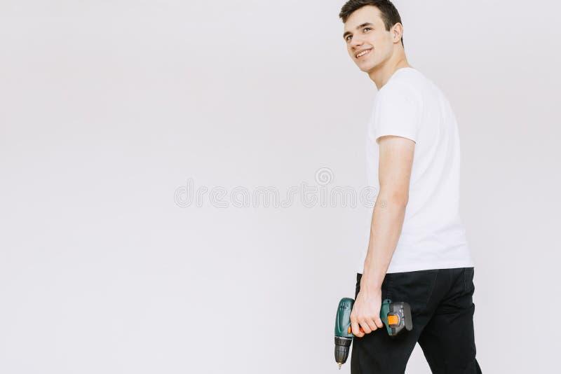 Un giovane tipo che tiene un cacciavite, un trapano con la sua mano Fondo bianco isolato fotografie stock