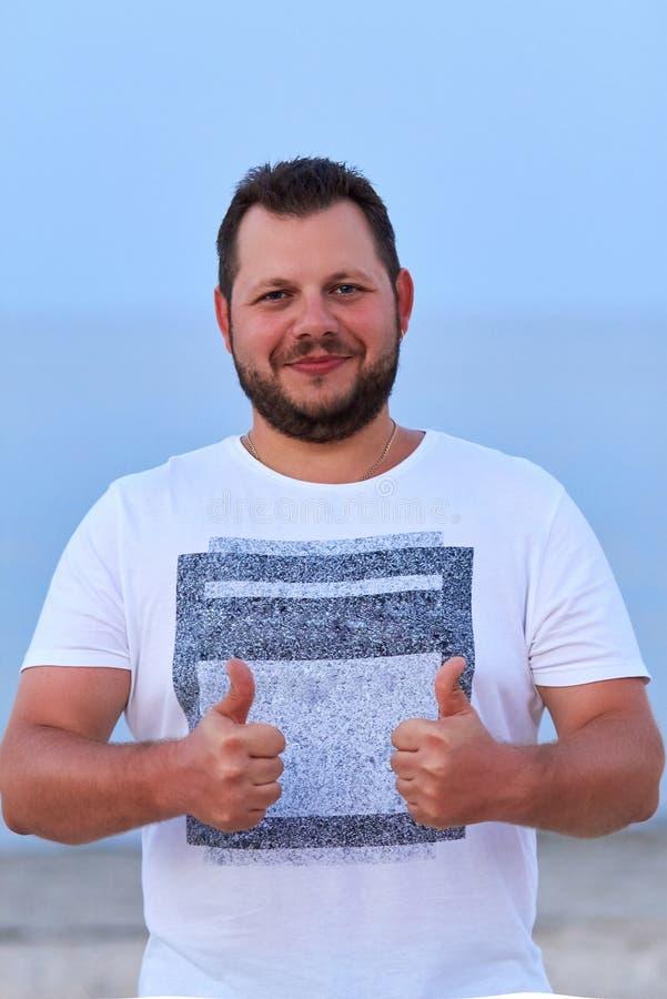 Un giovane tipo positivo bello sorride e mostra OKAY Ritratto della a fotografie stock libere da diritti