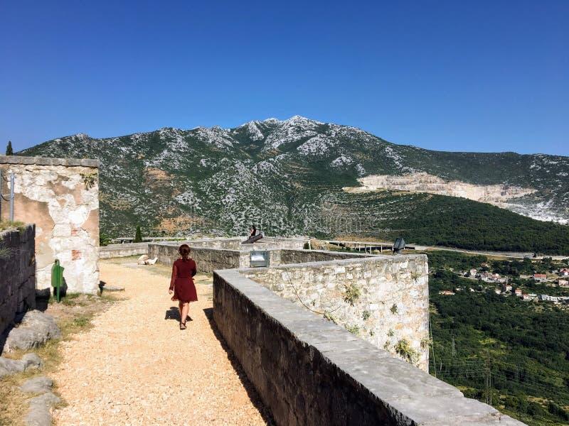 Un giovane turista femminile che cammina intorno alla fortezza medievale di Klis un bello giorno di estate fotografia stock libera da diritti