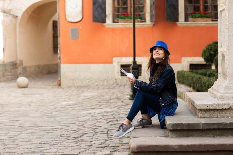 Un giovane turista si siede sulle scale nel vecchio cortile, vicino alla parete rossa a Leopoli l'ucraina fotografia stock libera da diritti