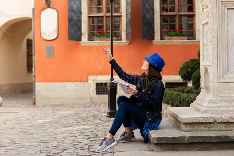 Un giovane turista si siede sulle scale nel vecchio cortile, vicino alla parete rossa a Leopoli l'ucraina immagini stock