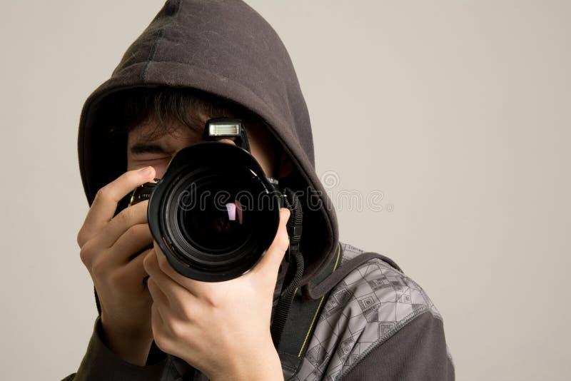 Un giovane in un cappuccio facendo uso di una macchina fotografica professionale fotografia stock libera da diritti