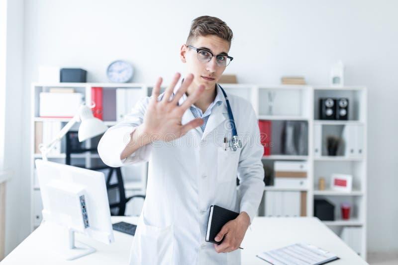Un giovane in una condizione bianca dell'abito nell'ufficio, mostra la sua mano e la tenuta del taccuino fotografie stock