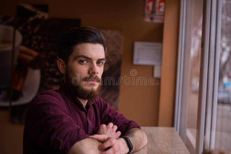 Un giovane uomo alla moda in caffetteria fotografia stock