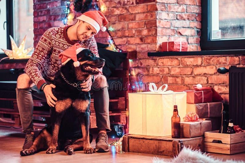 Un giovane uomo alla moda che tiene un contenitore di regalo mentre sedendosi con il suo cane sveglio in un salone decorato al te immagine stock
