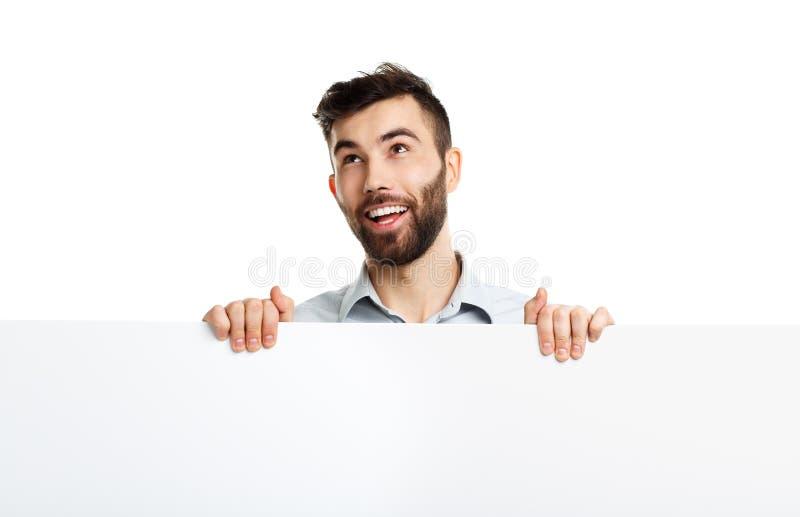 Un giovane uomo barbuto che mostra insegna in bianco, isolata sopra bianco fotografia stock libera da diritti