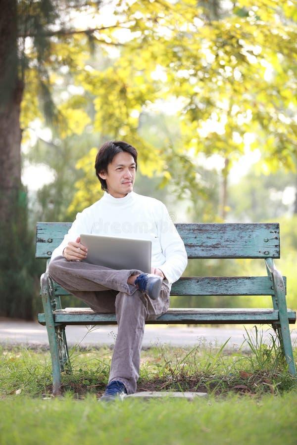 Un giovane uomo bello che per mezzo del computer portatile che si siede su un Ben fotografie stock