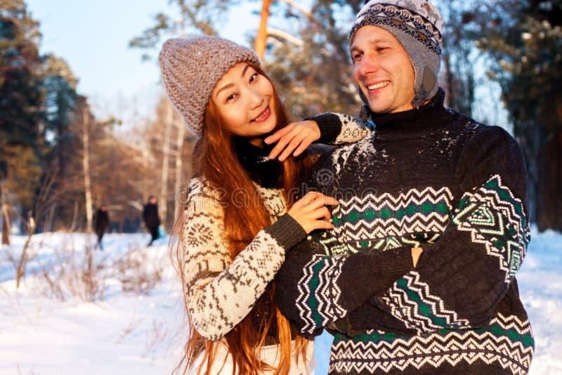 Un giovane uomo bello dell'aspetto europeo e una giovane ragazza asiatica in un parco sulla natura nell'inverno immagini stock libere da diritti