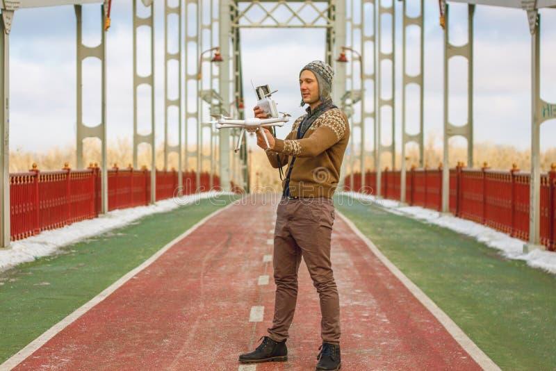 Un giovane uomo bello dell'aspetto europeo lancia un fuco nei precedenti di un cielo blu su un ponte nell'inverno fotografie stock