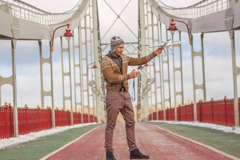 Un giovane uomo bello dell'aspetto europeo lancia un fuco nei precedenti di un cielo blu su un ponte nell'inverno immagine stock libera da diritti