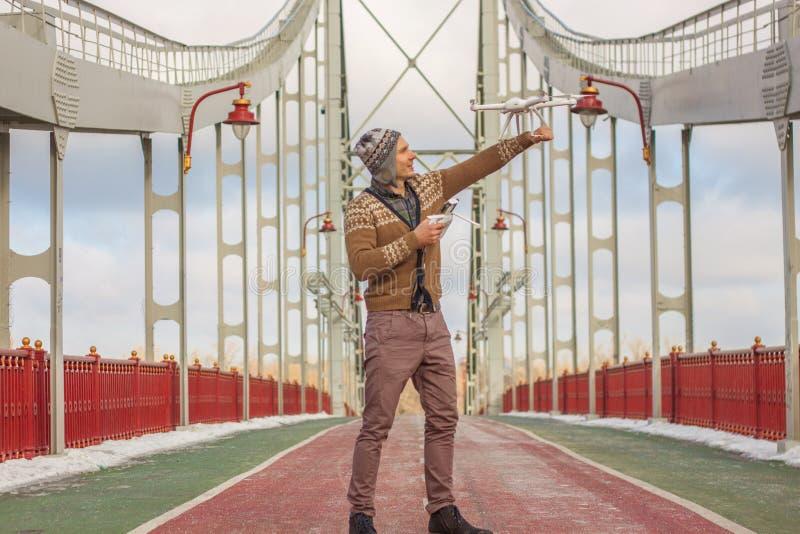 Un giovane uomo bello dell'aspetto europeo lancia un fuco nei precedenti di un cielo blu su un ponte nell'inverno fotografie stock libere da diritti