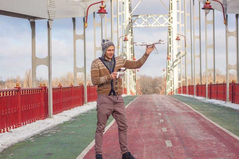 Un giovane uomo bello dell'aspetto europeo lancia un fuco nei precedenti di un cielo blu su un ponte nell'inverno fotografia stock libera da diritti