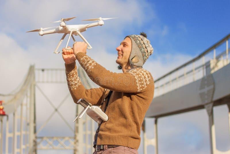 Un giovane uomo bello dell'aspetto europeo lancia un fuco nei precedenti di un cielo blu su un ponte nell'inverno immagini stock libere da diritti