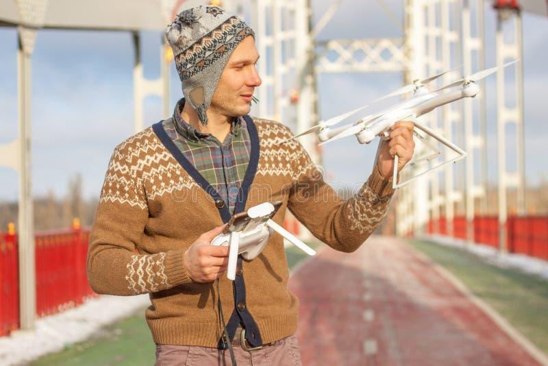 Un giovane uomo bello dell'aspetto europeo lancia un fuco nei precedenti di un cielo blu su un ponte nell'inverno immagini stock