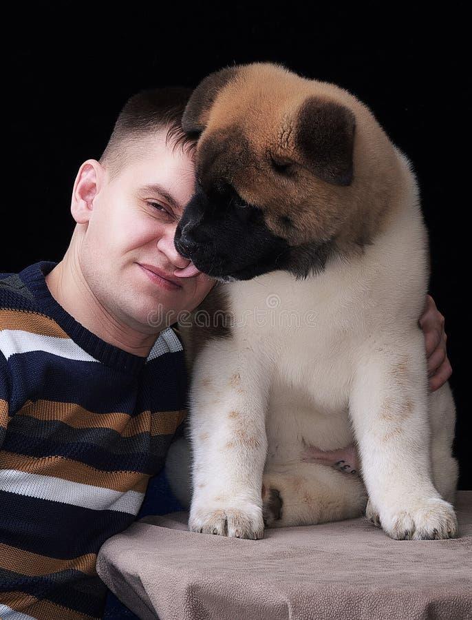 Un giovane uomo coraggioso con un cucciolo irsuto, il cane lecca il fronte del ` s dell'uomo fotografia stock libera da diritti