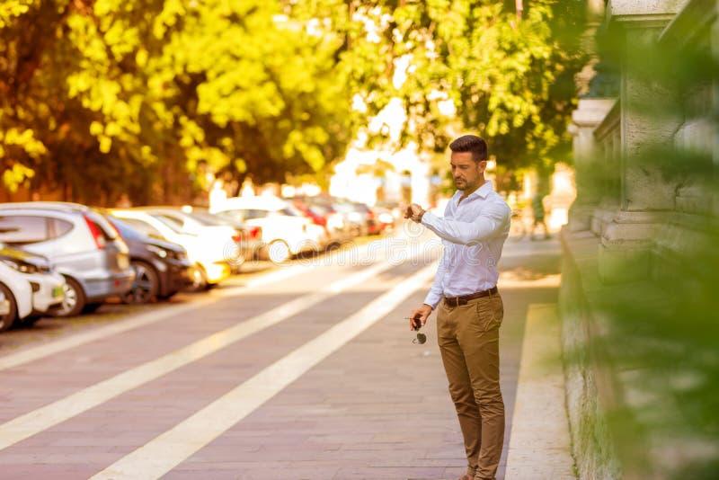 Un giovane uomo d'affari che sta e che controlla il tempo fotografie stock libere da diritti