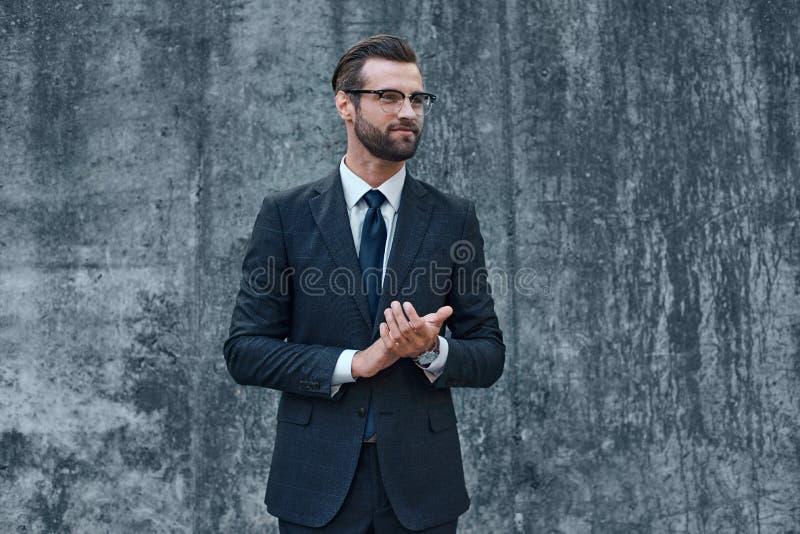 Un giovane uomo d'affari con i vetri e una barba applaude le sue mani fotografia stock libera da diritti