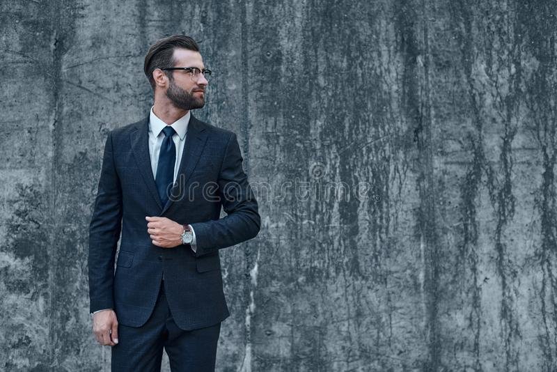 Un giovane uomo d'affari con i vetri e una barba guarda a sinistra fotografia stock libera da diritti