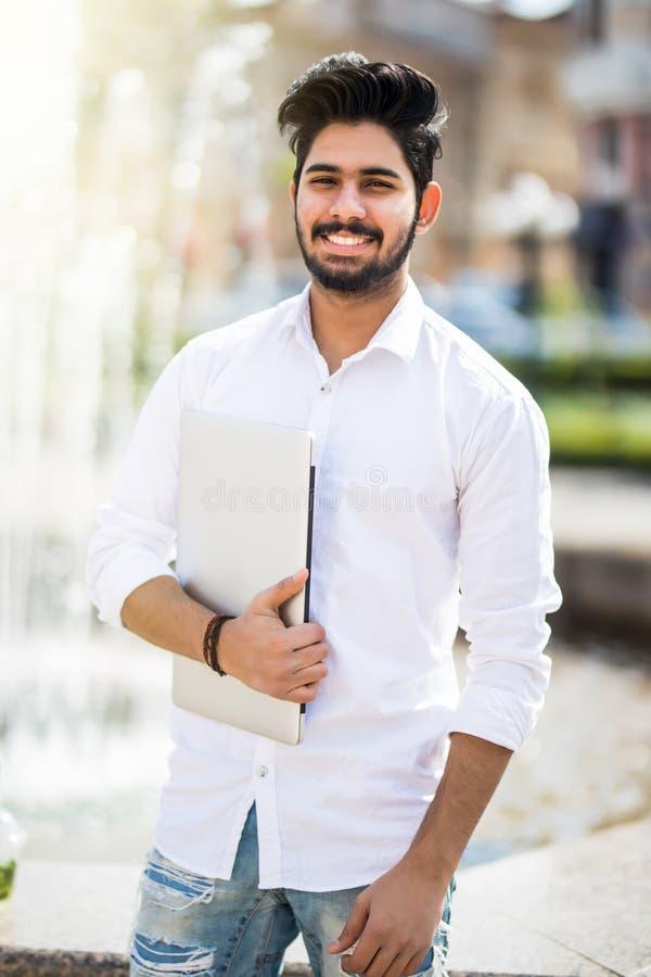 Un giovane uomo d'affari indiano bello che tiene il suo computer portatile mentre stando sulla via immagini stock libere da diritti