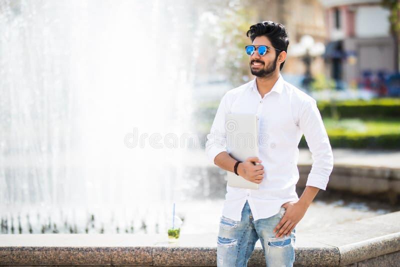 Un giovane uomo d'affari indiano bello che tiene il suo computer portatile mentre stando sulla via fotografia stock