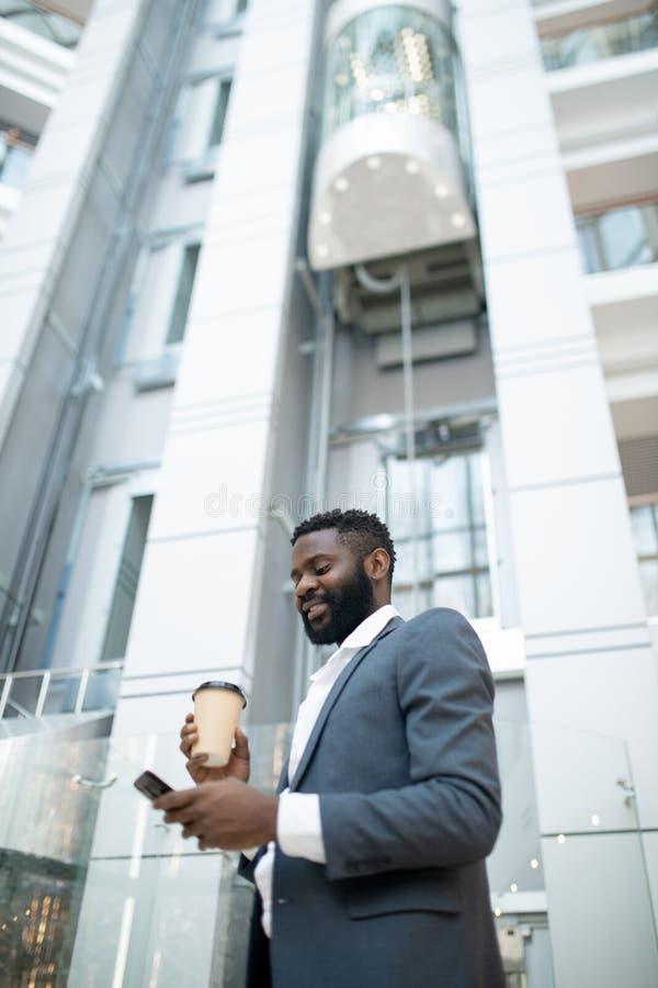 Un giovane uomo d'affari nero sorridente che controlla gli sms immagine stock libera da diritti