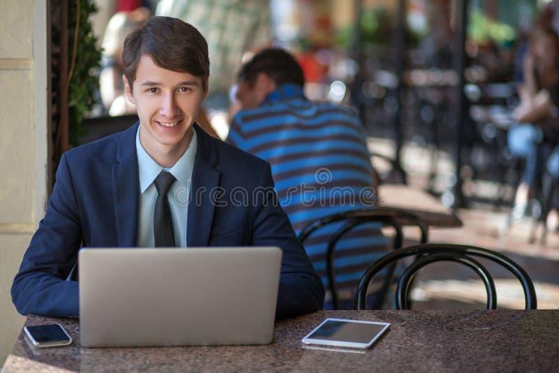 Un giovane uomo d'affari professionale bello rilassato che lavora con il suoi computer portatile, telefono e compressa in un caff fotografie stock