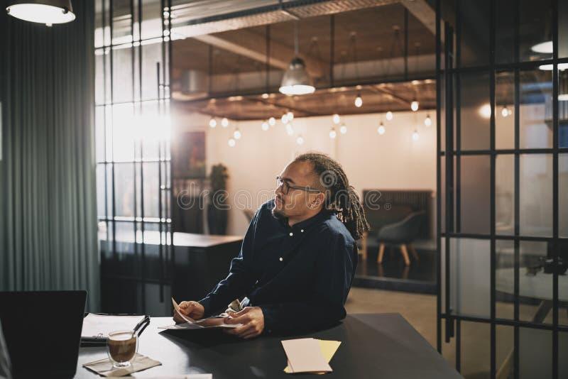 Un giovane uomo d'affari seduto a un tavolo in un ufficio moderno fotografia stock libera da diritti