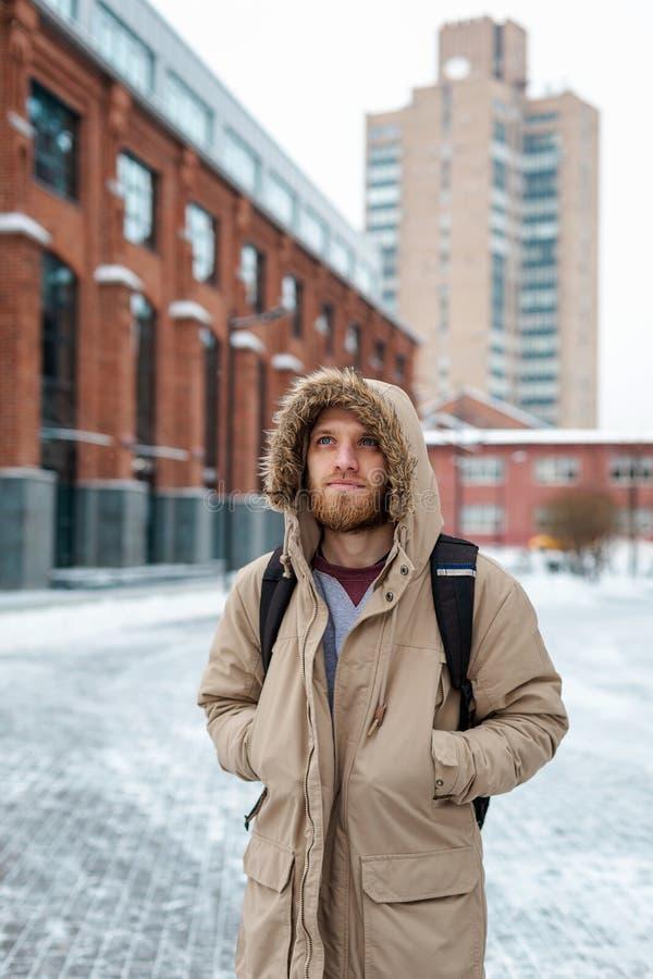 Un giovane uomo della barba cammina in un cappotto dell'inverno immagine stock