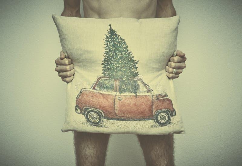 Un giovane uomo nudo copre il suo gallo di cuscino con un modello di tema di Natale affare dopo il nuovo anno fotografia stock libera da diritti
