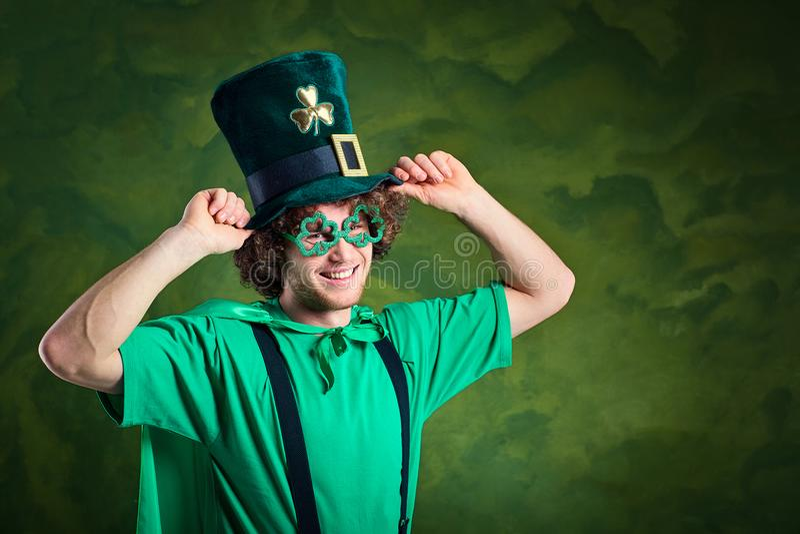 Un giovane uomo riccio-dai capelli nel vestito del ` s di St Patrick mostra il suo dito fotografie stock