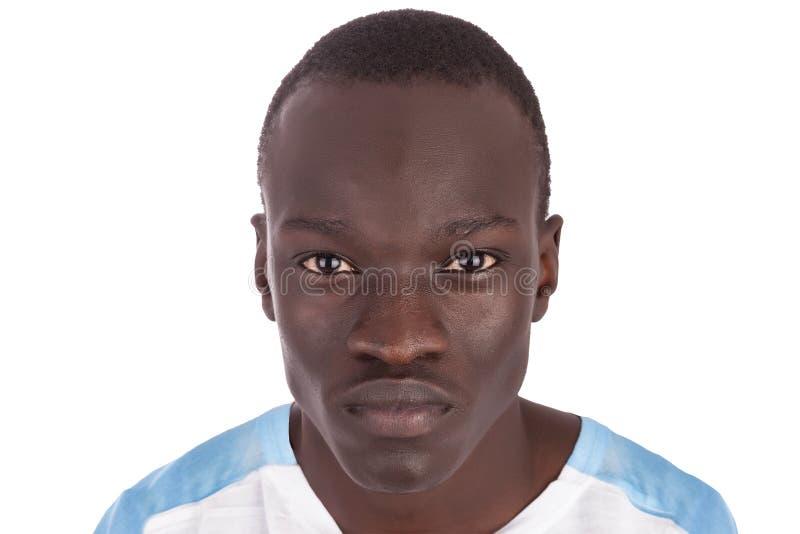 Un giovane uomo sudanese bello con un'espressione dolce che esamina direttamente la macchina fotografica nel pensiero immagini stock libere da diritti