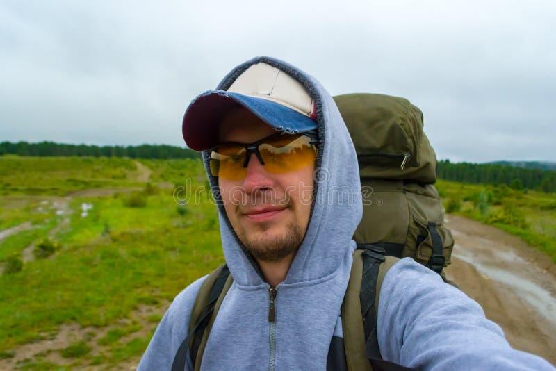 Un giovane uomo turistico con i baffi e la barba sul suo fronte viaggiano fotografia stock