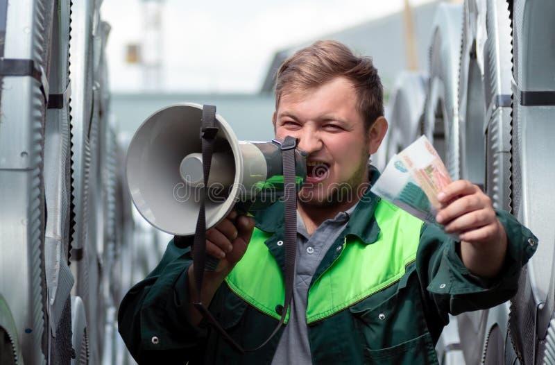 Un giovane in vestiti da lavoro grida fortemente in un altoparlante che invita per unirlo sul lavoro L'uomo dà le banconote come  immagine stock libera da diritti