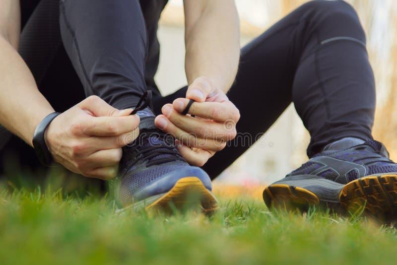 Un giovane in vestiti neri sta legando i pizzi sulle scarpe da tennis vicino su atleta di forma fisica che si siede sul campo spo immagine stock libera da diritti