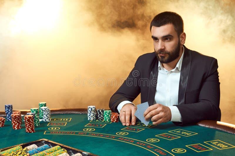 Un giovane in un vestito che si siede alla tavola della mazza Giochi dell'uomo Il giocatore alle carte da gioco della tavola di g fotografie stock libere da diritti
