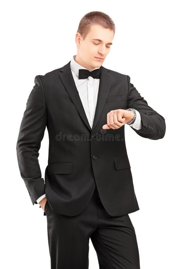 Un giovane in vestito nero con il farfallino che esamina orologio immagine stock libera da diritti