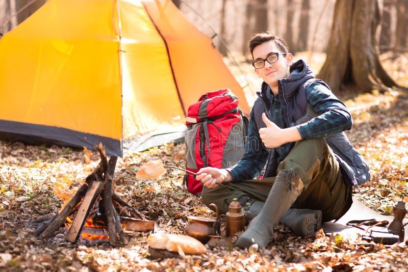 Un giovane viaggiatore nella foresta sta riposando vicino alla tenda ed alla prima colazione cucinata in natura immagini stock