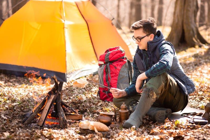 Un giovane viaggiatore nella foresta sta riposando vicino alla tenda ed alla prima colazione cucinata in natura fotografia stock