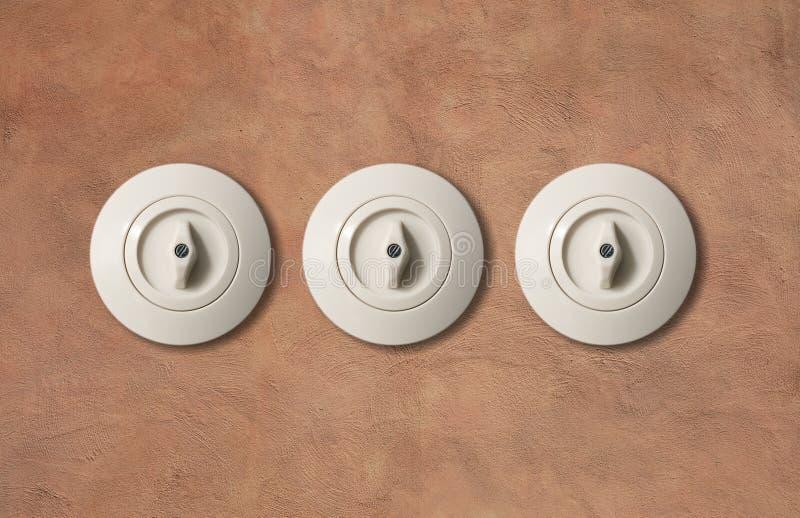 Un giro bianco d'annata di tre commutatori con il bottone sul contesto marrone chiaro della parete dello stucco primo piano, dett fotografia stock