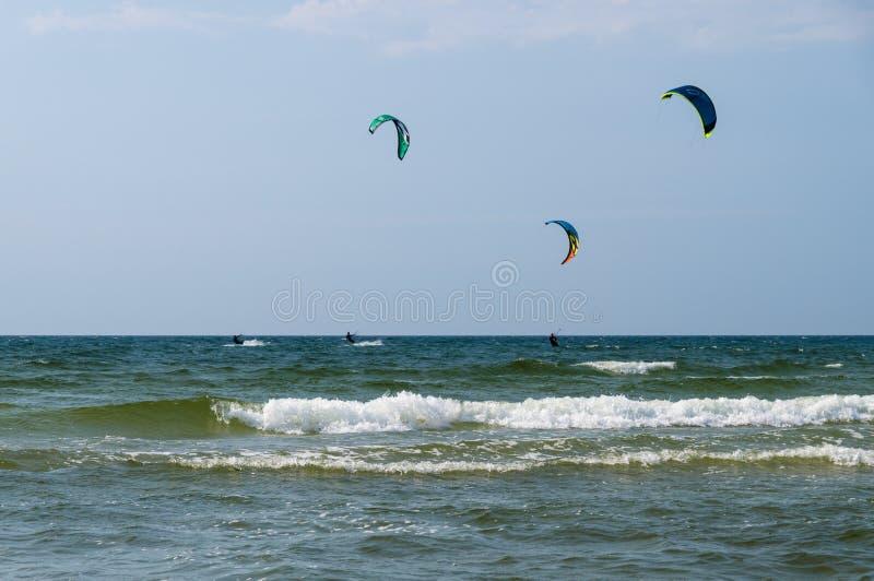 Un giro di tre kiters sulle onde del mare fotografia stock libera da diritti