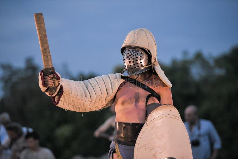 Un gladiatore che porta un costume romano antico tradizionale con lo schermo e la spada del casco fotografia stock libera da diritti