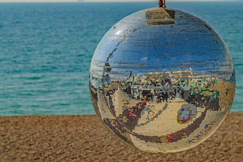 Un glitterball de bord de la mer se reflétant comme un visage de sourire photo stock