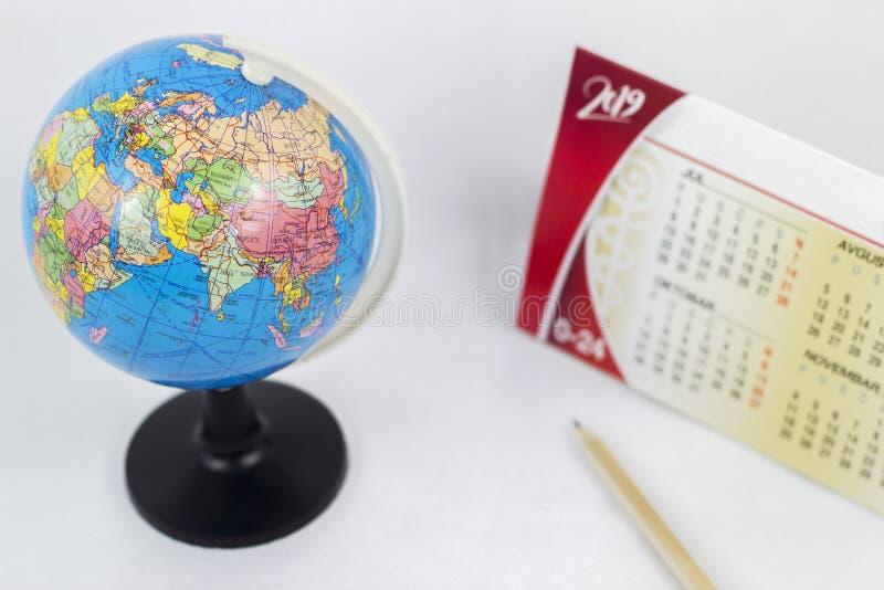 Un globe et un calendrier avec un stylo sur un fond blanc Foyer sur le globe images stock