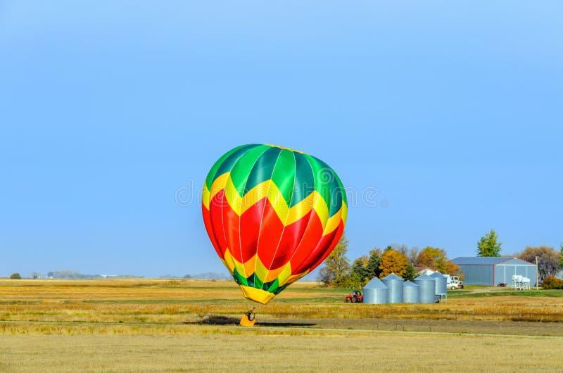 Un globo multicolor cerca de una granja saca en un cielo azul encima fotografía de archivo libre de regalías
