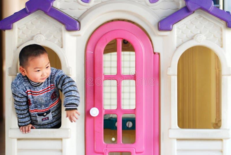 Un gosse à l'intérieur d'une maison de poupée images libres de droits