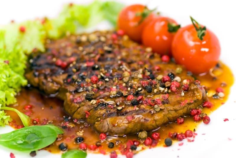 Un grain de poivre grillé - bifteck avec de la laitue de tomate images stock